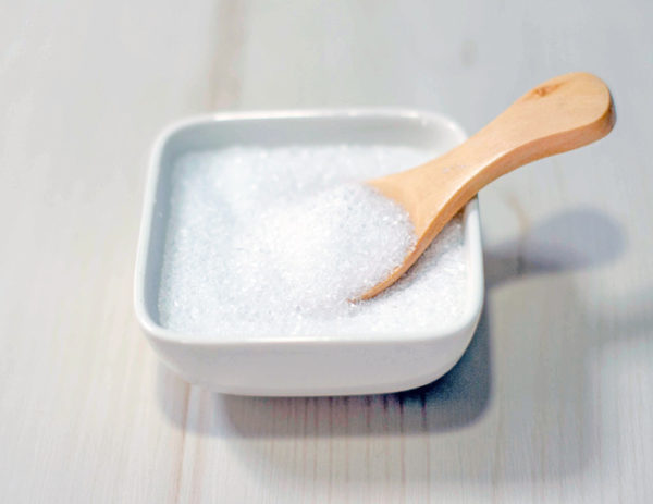 Epsom salts in a square bowl with a wood spoon