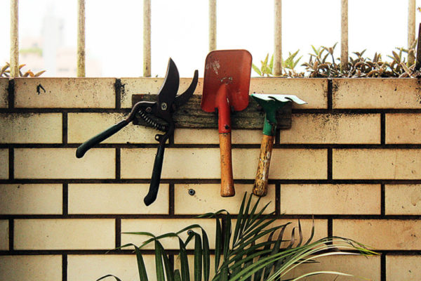 Garden hand tools against a brick wall