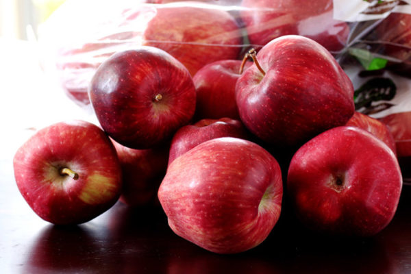 A pile of Red Delicious apples sitting on a dark wood table