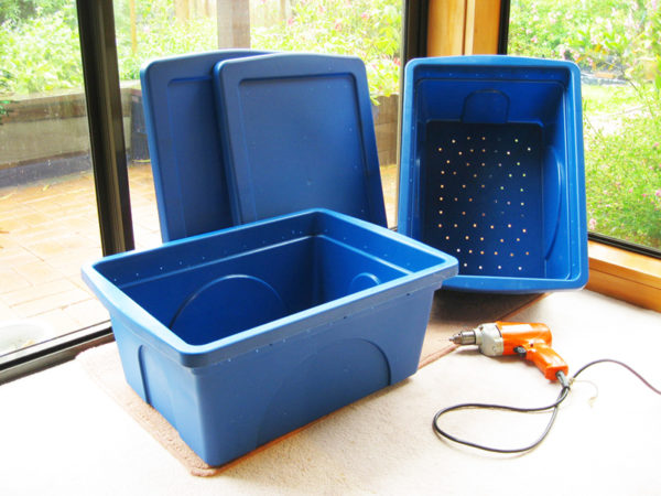 Vermicomposting set up with blue plastic bins and a drill