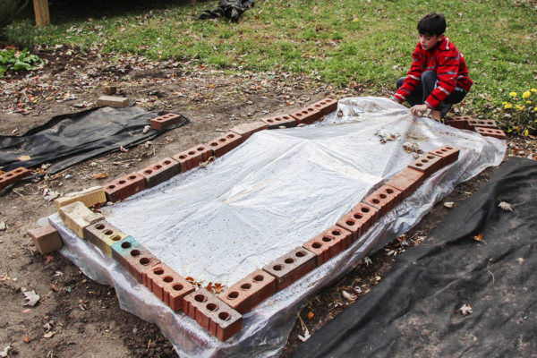 A basic cold frame being held shut by bricks with a boy lifting the plastic cover