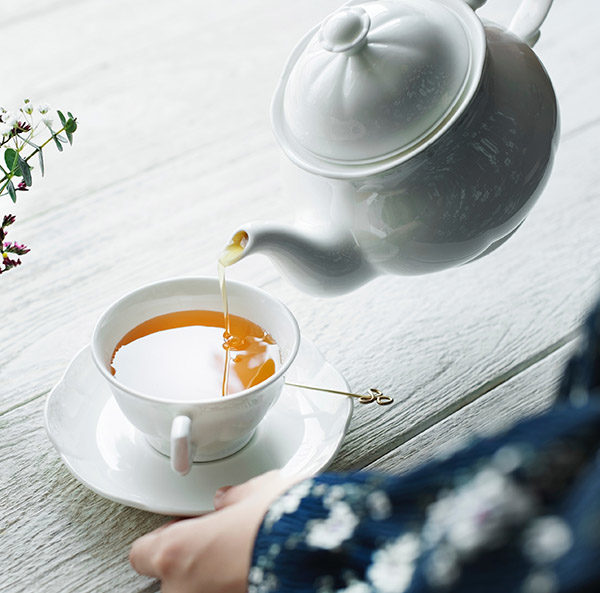 Tea being poured into a cup on a white saucer